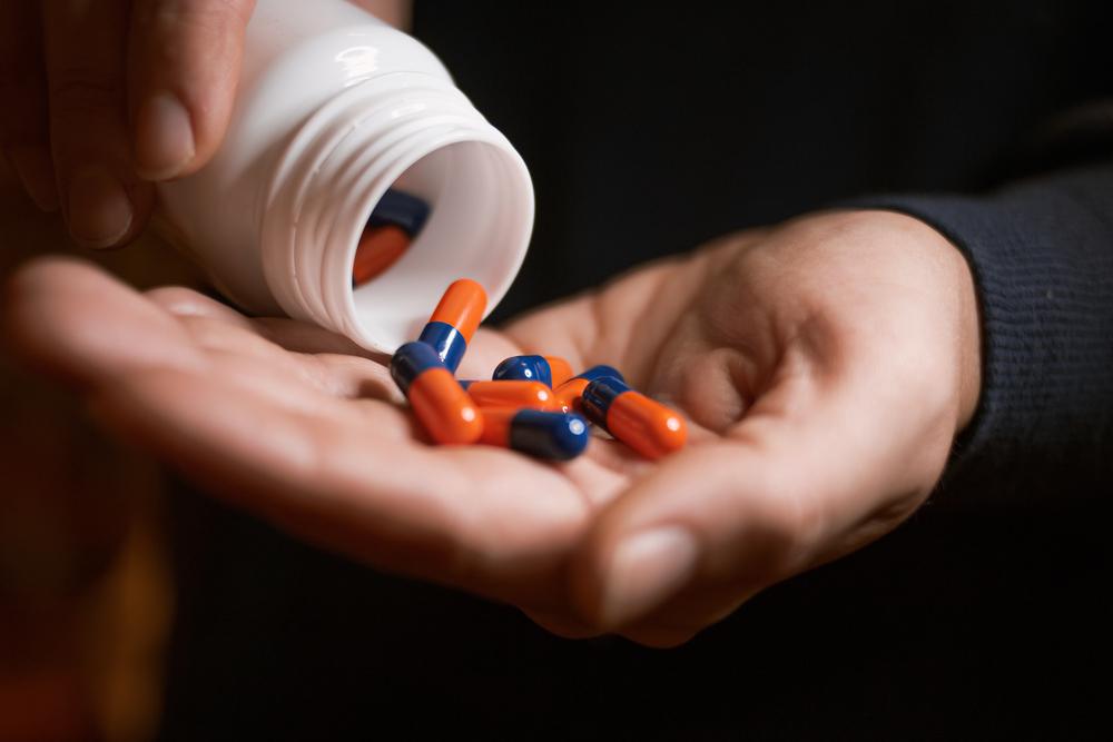 um homem segurando pote de remédios e remédios na palma da mão