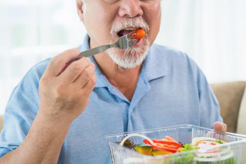 homem comendo tomate licopeno