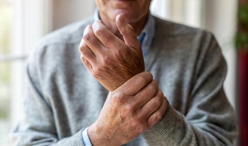 Homem idoso segura as mãos com dores nas juntas