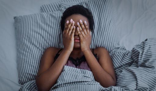 Mulher deitada na cama e aborrecida com a insônia