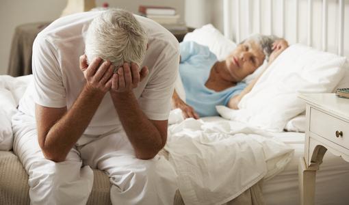 Homem com impotência sexual sentado na cama ao lado da esposa