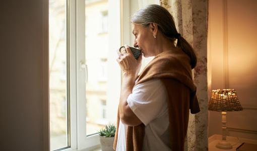 Mulher toma chá de carqueja em frente a janela